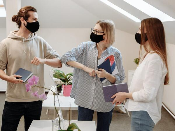 Employees wearing face masks encouraging each other