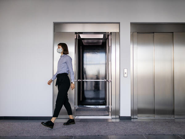 Woman wearing face mask walking out from the elevator
