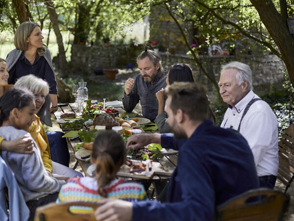 Large family sit around table eating