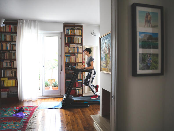 Man running on a treadmill in his library