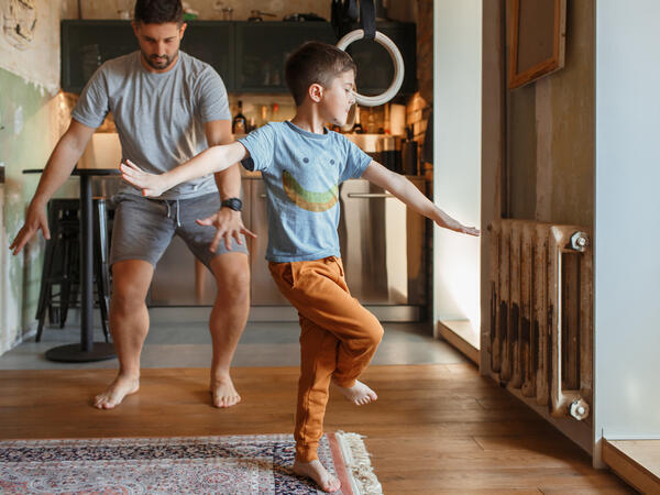 Father and son dancing in the living room