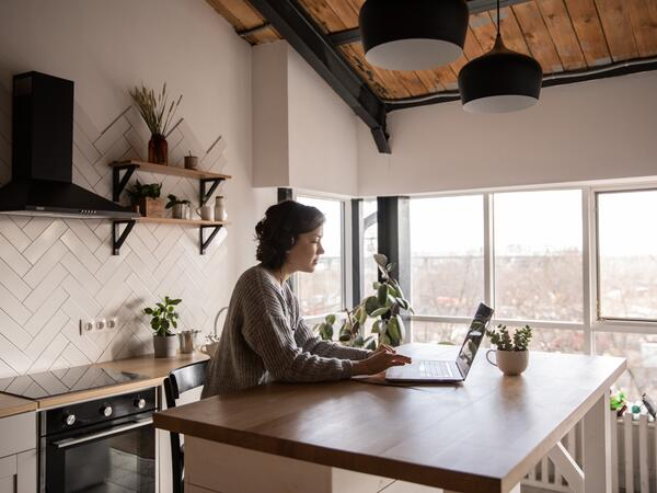 Woman working in kitchen on laptop