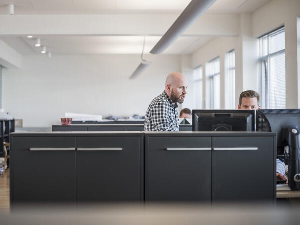 Coworkers collaborating at computer in open concept office
