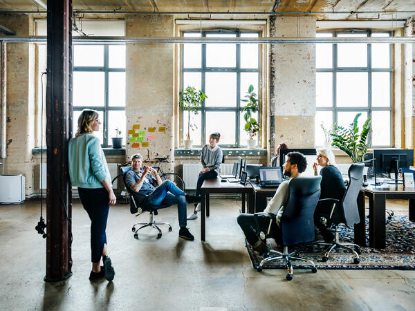 Coworkers all chatting in open concept office