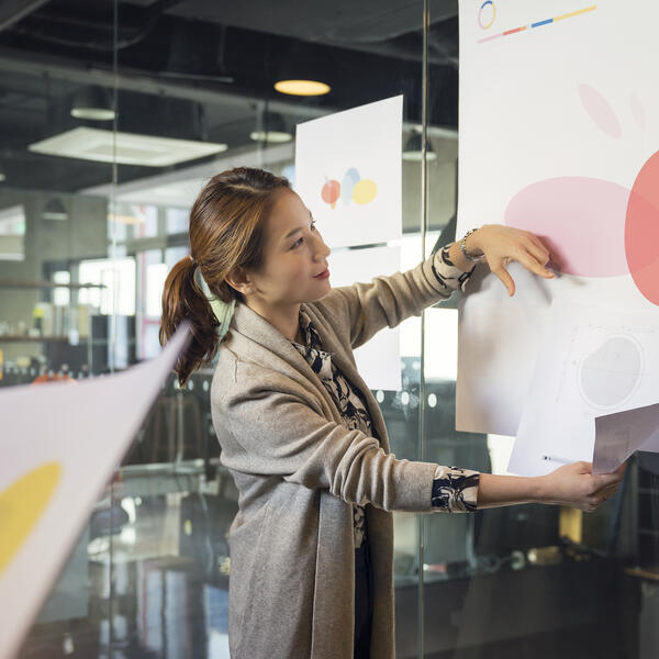 Woman presenting large illustration in meeting